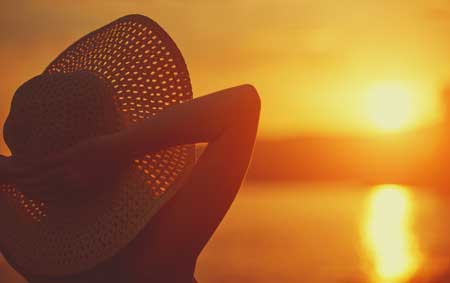 41423022 - beauty happy woman in her hat is back and admire the sunset over the sea on the beach
